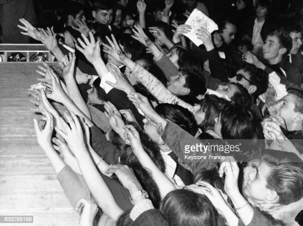 Adolescents manifestant leur enthousiasme et leur joie pendant un concert d'une vedette de variété à Paris France 21 novembre 1963