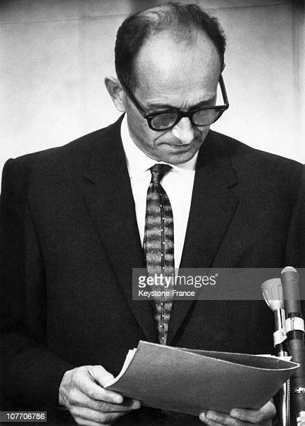 Adolf Eichmann In A BulletProof Cabin Puts On Earphones To Hear The Reading Of The Act Of Accusation Against Him To The Left Is His German Lawyer...