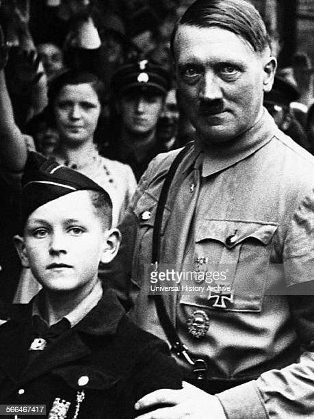 Adolf Hitler 18891945 German Nazi leader seen standing with a young Hitler Youth Member 1934