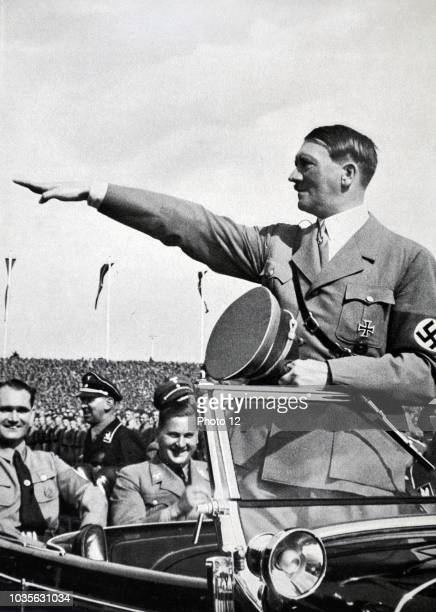 Adolf Hitler 18891945 German politician and the leader of the Nazi Party salutes Hitler Youth Rally Rudolf Hess and Baldur von Schirach sit near...