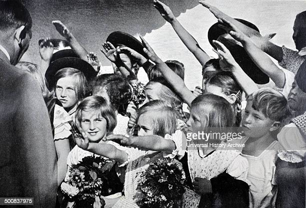 Adolf Hitler 18891945 German politician and the leader of the Nazi Party saluted as he greets young children