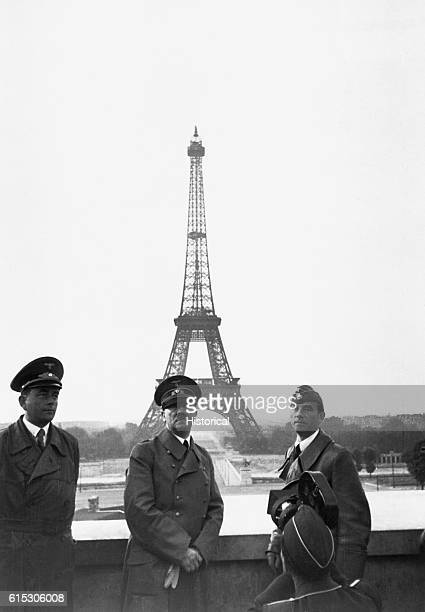 Adolf Hitler accompanied by his chief architect and adjutant Albert Speer and sculptor Arno Breker stands on a balcony before the Eiffel Tower Hitler...