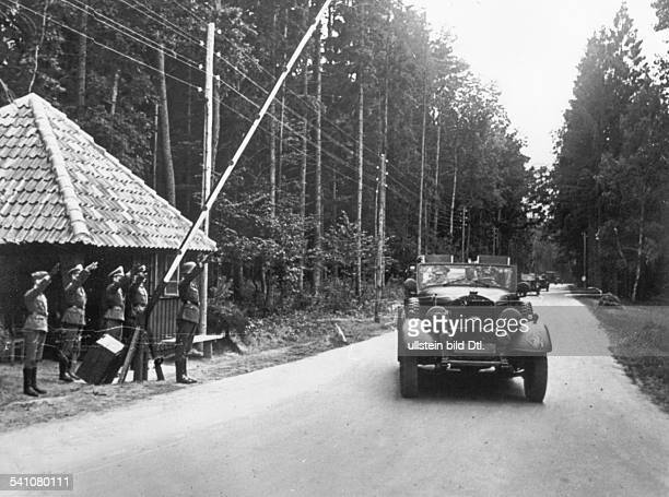 Adolf Hitler and a autocade pass the guards at his headquarters in Rastenburg East Prussia undated