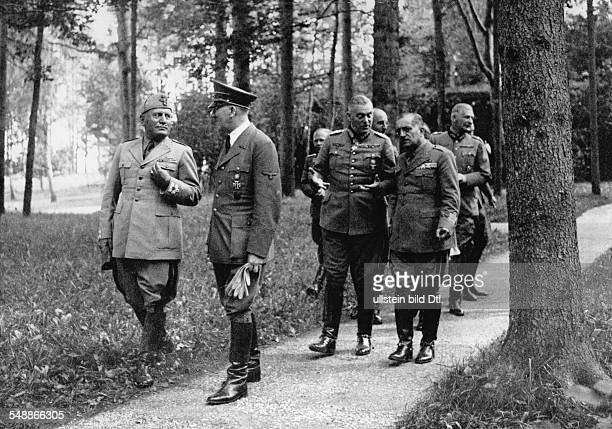 Adolf Hitler and Benito Mussolini in the area of Hitler's headquarters 'Wolfsschanze' near Rastenburg in East Prussia; following them from the left:...