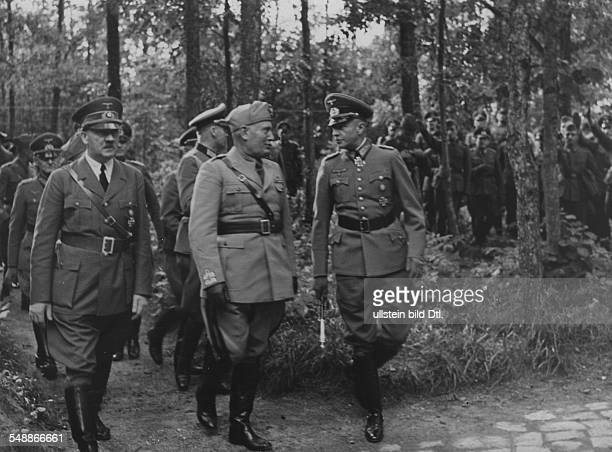 Adolf Hitler and Benito Mussolini in the outdoors near the headquarters of the army in the Mauerwald near Angerburg in East Prussia on the right...