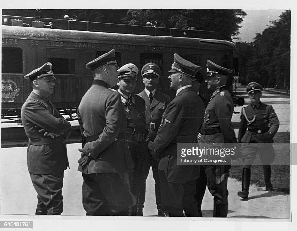 Adolf Hitler and Hermann Goering stand with military officers near the railroad car in which the 1918 armistice was signed