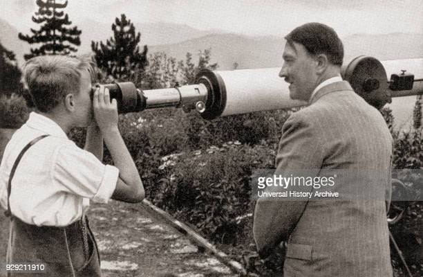 Adolf Hitler at his residence in Obersalzberg Bavaria Germany in 1936 watching a boy observing the Unterberg Mountain through a telescope Hitler...