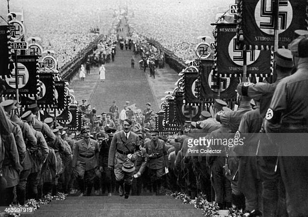 Adolf Hitler at the Bückeberg Harvest Festival Germany 1 October 1934 Hitler climbing steps between ranks of Nazis holding swastika banners Huge...