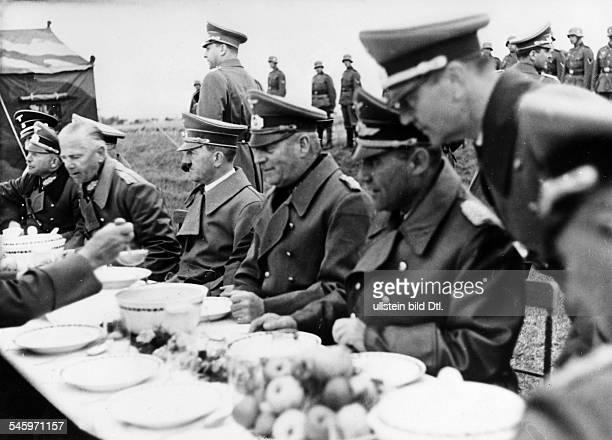 Adolf Hitler bei einem Essen aus derFeldküche mit Offizieren der deutschenWehrmacht in der Nähe von Karlsbad nebenHitler nach links die Generäle...