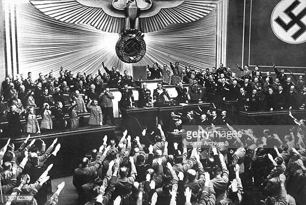 Adolf Hitler center left raises his arm in salute as he accepts the ovation of the Reichstag after announcing the peaceful acquisition of Austria in...