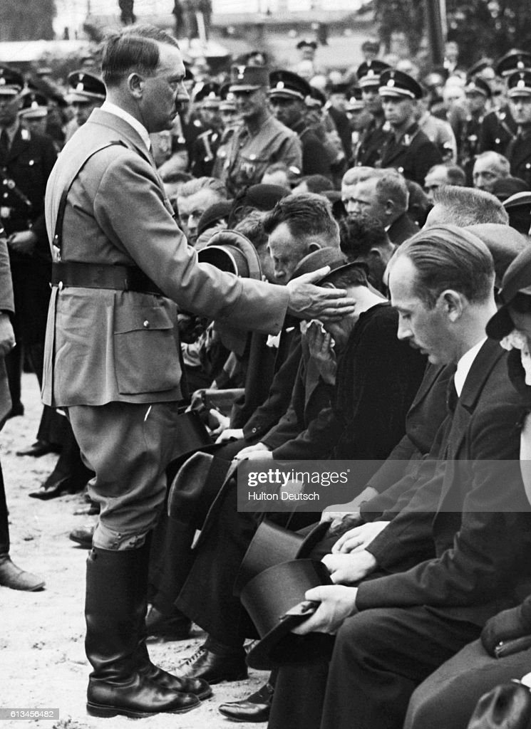 Adolf Hitler comforts a crying woman at a funeral in Reinsdorf. | Location: Reinsdorf, Germany.