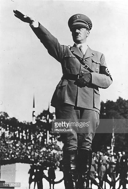 Adolf Hitler , dressed in military attire and giving the Nazi salute, early twentieth century.