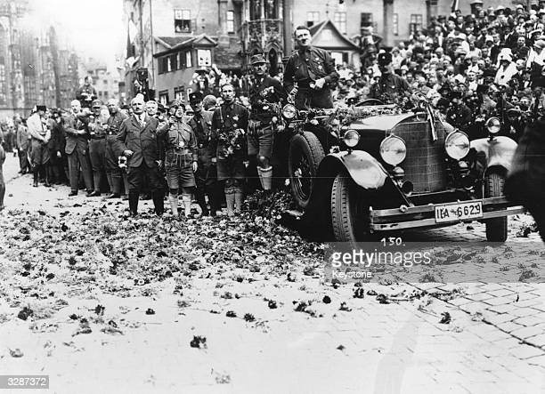 Adolf Hitler drives along a flower strewn road after a rally at Nuremberg