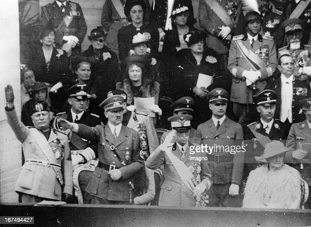 Adolf Hitler during his visit to Italy with Benito Mussolini and King Victor Emmanuel III Sitting Queen Elena In the second row Rudolf Hess and...
