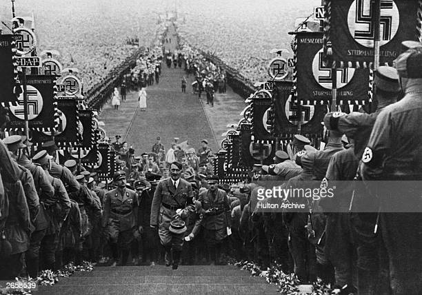 Adolf Hitler German dictator ascending the steps at Buckeberg flanked by bannercarrying storm troopers who display the Nazi swastika