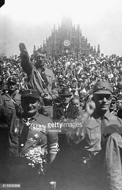 Adolf Hitler gives the Nazi salute at a Party rally in Nuremburg Germany ca 1928 From the Heinrich Hoffman Collection