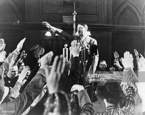 Adolf Hitler gruesst von einerRednertribuene im Muenchener Hofbraeuhausdie versammelten alten Parteimitgliederim Hintergrund rechts hinter...