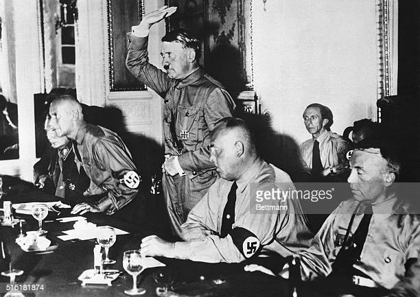 Adolf Hitler leader of the Nazi Party presided over a meeting of 230 Nazi members taking the oath of allegiance after the meeting Left to right...