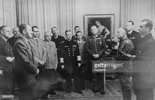 Adolf Hitler left receiving Romanian Premier Ion Antonescu at the Reich chancellery to sign his country into the axis Left to right from Hitler...