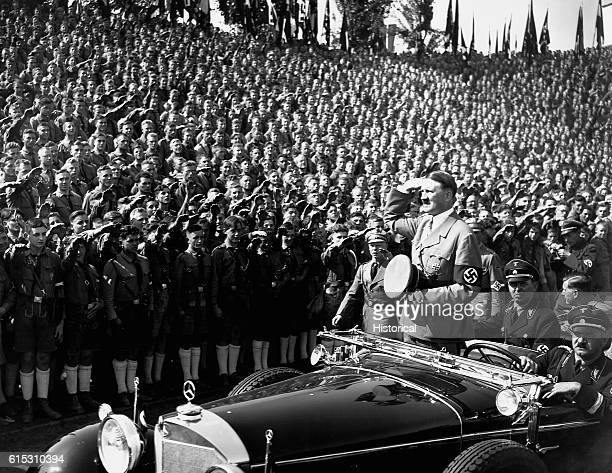 Adolf Hitler salutes a huge crowd of Hitler Youth as he is driven by in a motorcar