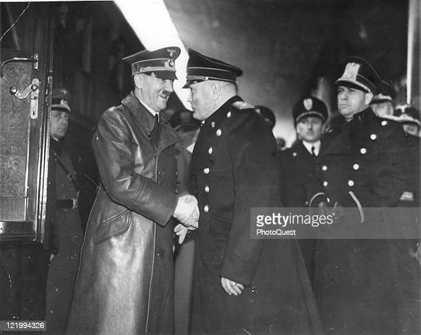 Adolf Hitler, smiling broadly, gives a firm handshake to Benito Mussolini, during a meeting to discuss the war, held at Brenner Pass railway station,...