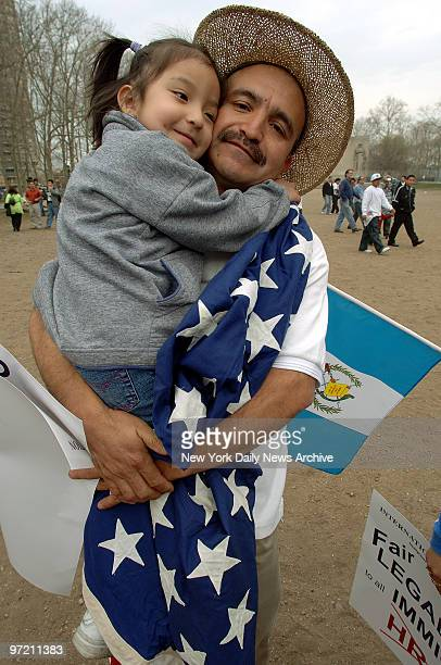 Adolfo Barrios of Guatemala cuddles daughter Danielle before the two headed across the Brooklyn Bridge into Manhattan with thousands of legal and...