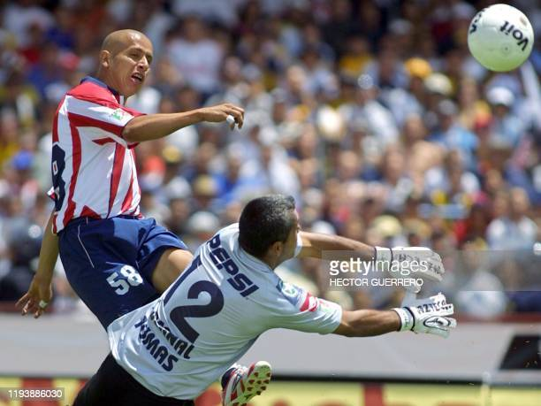 Adolfo Bautista de Chivas patea el balón ante la marca del portero de Pumas Sergio Bernal durante el partido en ciudad de México el 28 de marzo de...