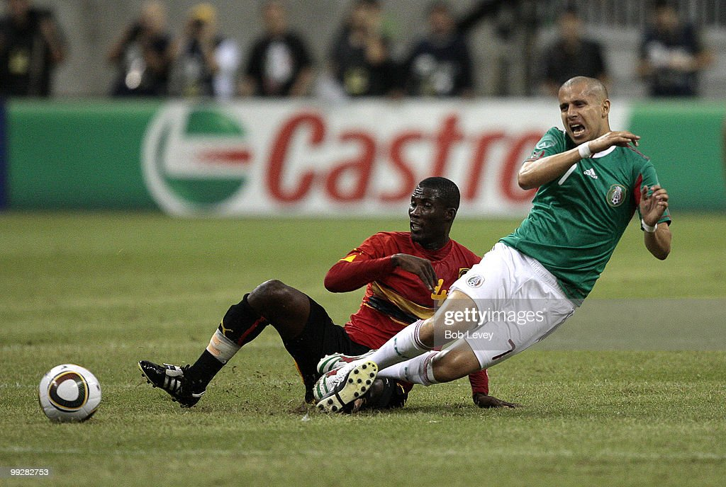Adolfo Bautista #7 of Mexico is brought down from behind by Francisco de Asis #4 of Angola at Reliant Stadium on May 13, 2010 in Houston, Texas.