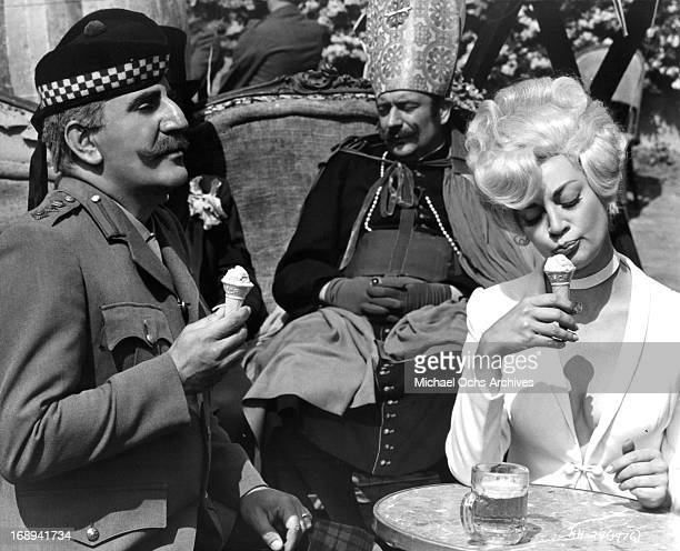 Adolfo Celi eats ice cream with Francoise Christophe in a scene from the film 'King Of Hearts' 1966