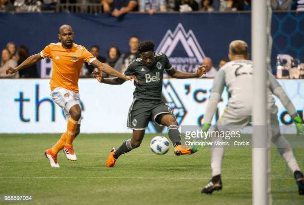 Adolfo Machado of Houston Dynamo chases Alphonso Davies of Vancouver Whitecaps who shoots on goalkeeper Joe Willis of Houston Dynamo at BC Place on...