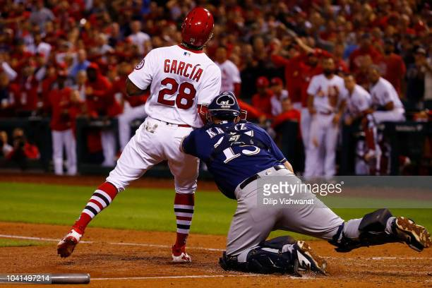 Adolis Garcia of the St Louis Cardinals is tagged out at home plate by Erik Kratz of the Milwaukee Brewers in the eighth inning at Busch Stadium on...