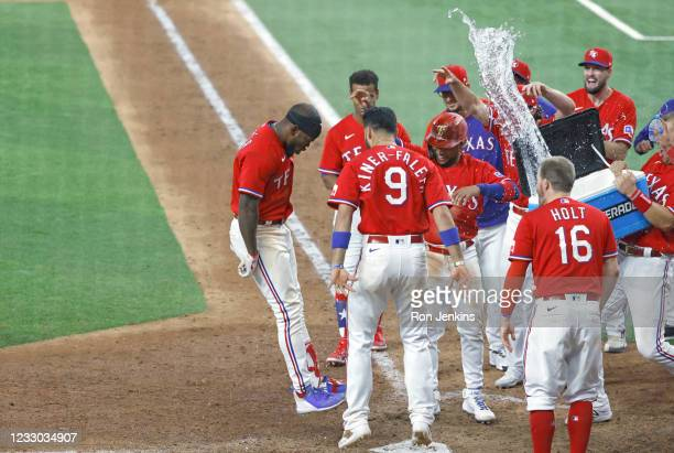 Adolis Garcia of the Texas Rangers and his teammates celebrate his three run walk-off home run against the Houston Astros during the tenth inning at...