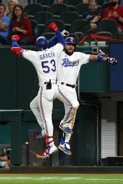 Adolis Garcia of the Texas Rangers celebrates with Isiah Kiner-Falefa after a solo home run to tie the game against the Seattle Mariners in the...