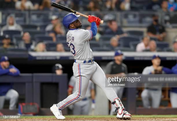 Adolis Garcia of the Texas Rangers follows through on a fifth inning run scoring sacrifice fly against the New York Yankees at Yankee Stadium on...