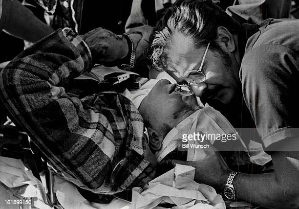 OCT 6 1973 OCT 7 1973 Adolph Coors IV Is Comforted As He Lies On Stretcher Following Accident Coors and the other driver Gary Thrall were reported in...