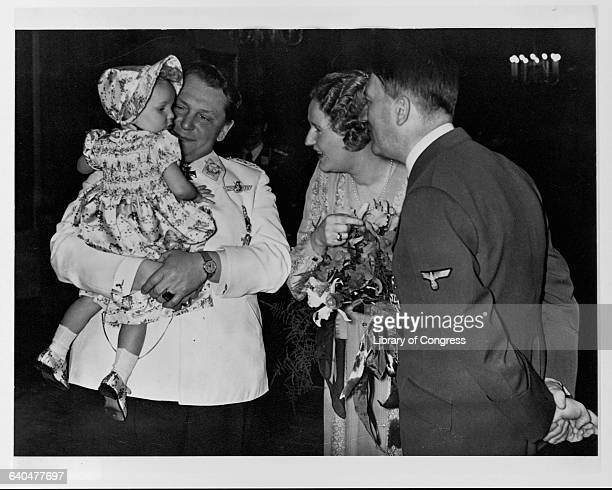 Adolph Hitler at Hermann Goering's birthday party, with Goering's wife Emmy and baby daughter Edda.