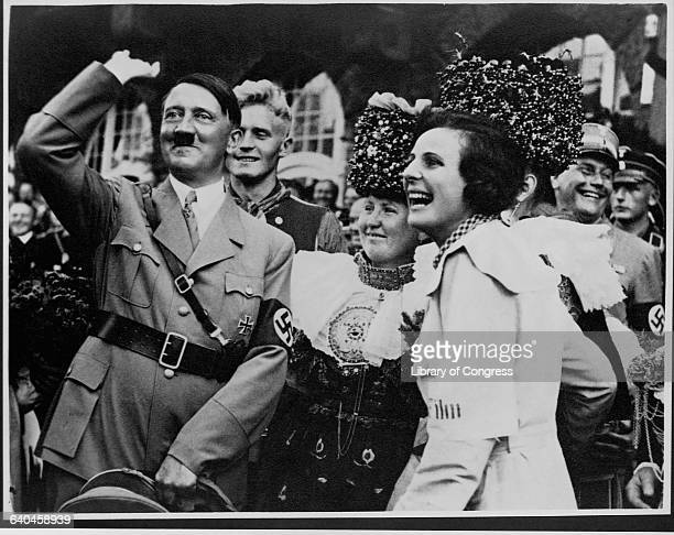 Adolph Hitler gives a Nazi salute, as German men and women look on and laugh.
