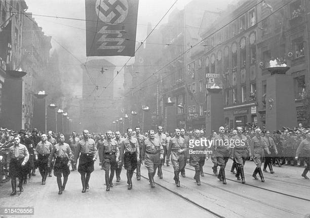Adolph Hitler marches with members of his Third Reich during the annual celebration of the Munich Beer Cellar Putsch of 1923 reenacting their...