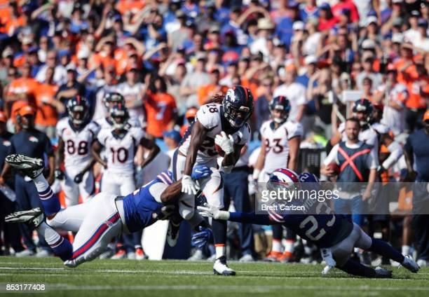 Adolphus Washington and Micah Hyde of the Buffalo Bills attempt to tackle Jamaal Charles of the Denver Broncos during an NFL game on September 24...