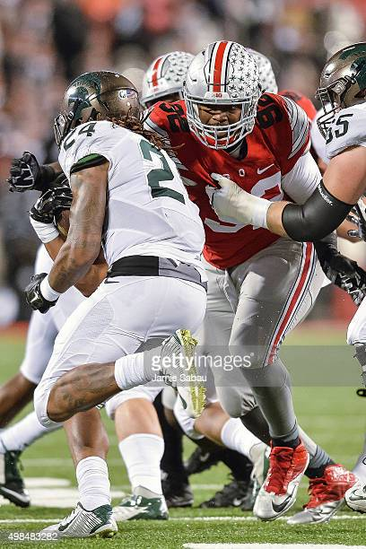 Adolphus Washington of the Ohio State Buckeyes makes a tackle on Gerald Holmes of the Michigan State Spartans at Ohio Stadium on November 21 2015 in...