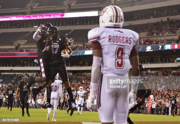 Adonis Jennings celebrates with Kenny Yeboah of the Temple Owls celebrates in front of Isaiah Rodgers of the Massachusetts Minutemen after scoring a...