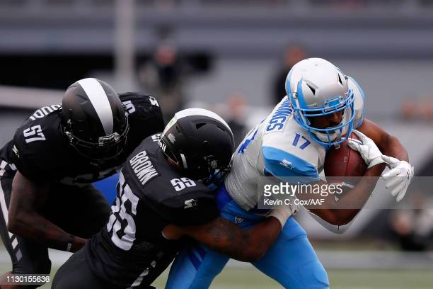 Adonis Jennings of Salt Lake Stallions is brought down by Jonathan Massaquoi and Beniquez Brown of the Birmingham Iron during an Alliance of American...