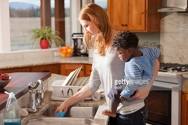 adopted boy watches mother wash dishes - adoptie stockfoto's en -beelden