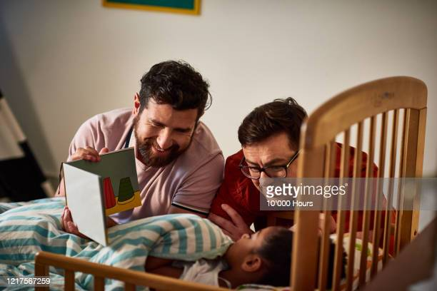 adoptive fathers reading bedtime story to daughter - 40 44 years stock pictures, royalty-free photos & images