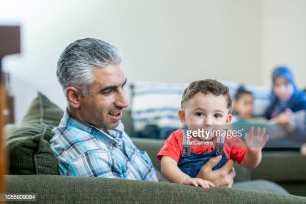 Adorable 1 year old boy waving his hand and sitting on his father's lap