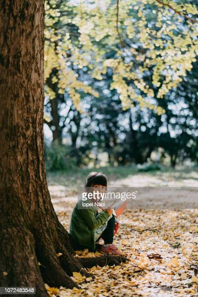 Adorable 4 year old girl sitting under ginkgo tree with book in autumn