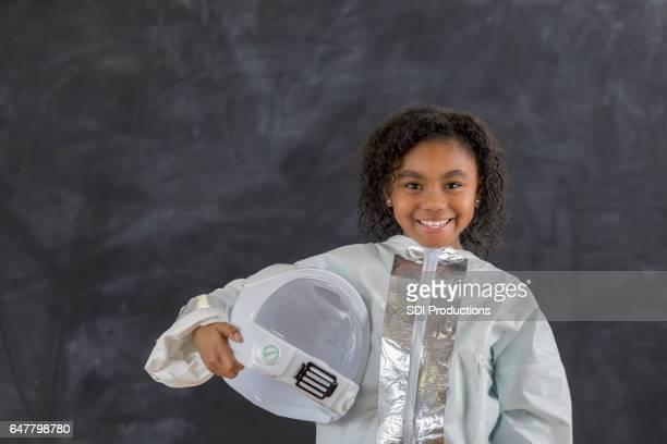 Adorable African American schoolgirl in astronaut costume