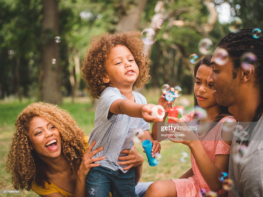 Adorable african-american curly haired toddler blows soap bulles : Stock Photo