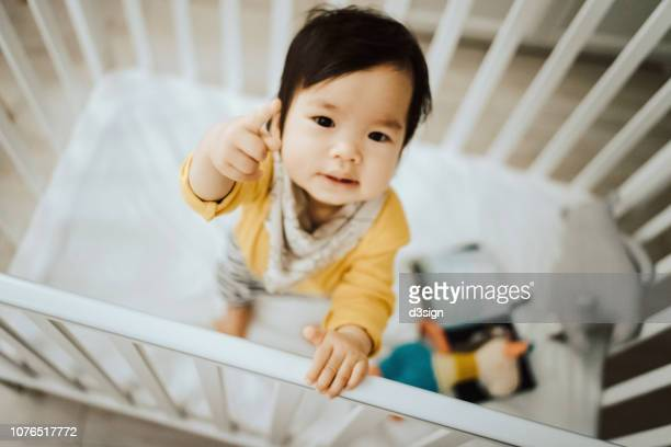 adorable asian baby girl standing in her crib and pointing away with fingers - baby pointing stock photos and pictures
