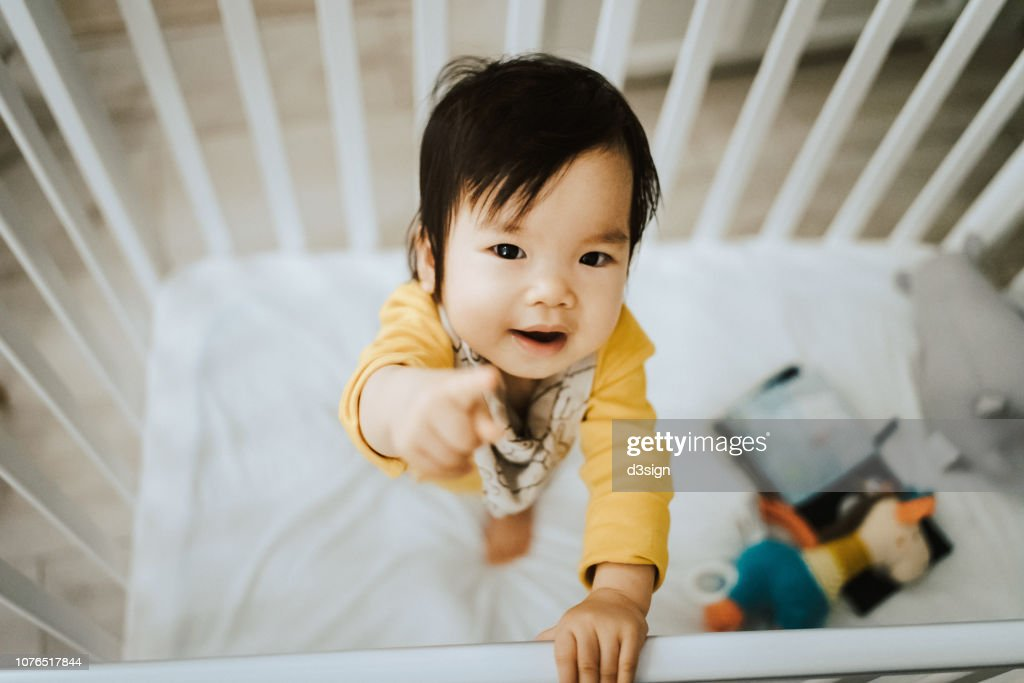 Adorable Asian baby girl standing in her crib and pointing away with fingers : Stock Photo